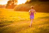 Young woman running outdoors on a lovely sunny summer evening (shallow DOF; color toned image)
