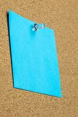 stock photo of oblique  - Blank sheet of blue paper with copyspace pinned up on a cork bulletin board with a thumb tack viewed at an oblique angle from below - JPG