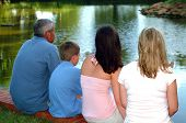 Family Of Four Looking At Pond