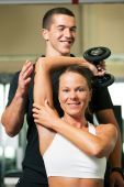 foto of personal trainer  - Woman with her personal fitness trainer in the gym exercising with dumbbells - JPG