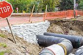 stock photo of sandbag  - White sandbag bags are full with sand in wall formation to hold the Earth near traffic road - JPG