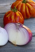 stock photo of boeuf  - Coeur de Boeuf Tomatoes and large red Onions from Weekly Market in South France on a old wooden Table - JPG