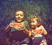 picture of melon  - two kids eating watermelon done with a retro vintage instagram filter - JPG