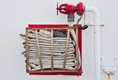 image of firehose  - A fire hose stored on a wall - JPG