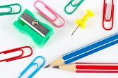 Pencil paperclips sharpener and pushpin on white desktop