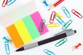 Pen pencil paperclips pushpins and multicolored stickers on white desktop