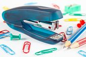 Stapler and multicolored stationery supplies on white desktop