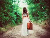 Young Woman With Suitcase In Hand Going Away By Rural Road