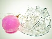 Pink velvety New Year's ball and elegant tinsel with a retro effect