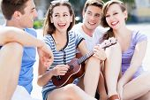 Young woman playing ukulele friends