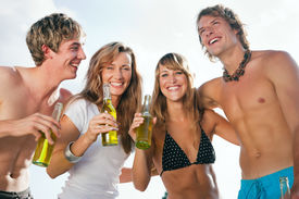 pic of beach party  - Group of four very beautiful people celebrating hot party on the beach in the summer of their lives  - JPG