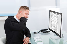 image of stiff  - Businessman studying an online spreadsheet on a desktop monitor rubbing his neck in confusion or to ease stiffness - JPG