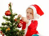 picture of new years baby  - baby Santa girl decorating a new year tree - JPG