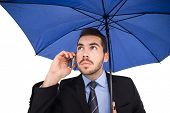 Serious businessman under umbrella phoning on white background