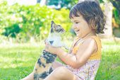 young child girl having fun with cat, little kitten on natural background
