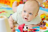 stock photo of playmate  - a baby on the carpet with toys - JPG