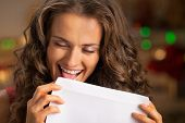 Portrait Of Happy Young Housewife Licking Envelope