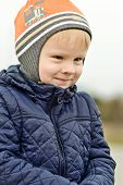 stock photo of cun  - toddler boy outdoors with a cunning face - JPG