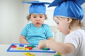 Happy little girl and serious boy in blue graduation hat sitting at table and playing with children magnetic board with colored letters