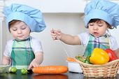 Two small children boy and girl in kitchen apron and cap play at table with vegetables