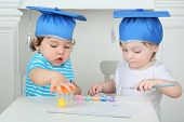 Young girl and boy in blue graduation hats paint colors at table