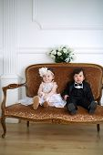 Small beautiful girl in white dress and her friend in black suit sitting on couch
