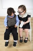 Little girl in black dress with mobile phone sitting on white chair next to boy with glasses and tablet computer