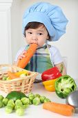 Little boy with serious face in kitchen apron and cap eating carrot