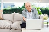 Happy senior man gesturing while video chatting on laptop at nursing home porch
