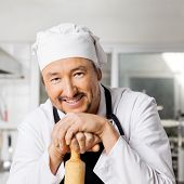 Portrait of happy male chef leaning on rolling pin in commercial kitchen