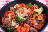 Braised wild mushrooms with vegetables and spices in pan on tablecloth