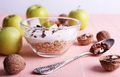 Oatmeal with yogurt in bowls/bowl, apples and walnuts on pink wooden table on light background