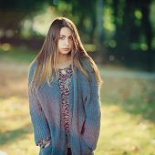 Outdoors portrait of a young handsome woman with long hair in knitted cardigan