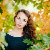 Outdoors portrait of serious beautiful lady in autumn leaves
