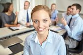 business, people and teamwork concept - smiling businesswoman with group of businesspeople meeting in office