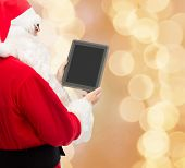 christmas, advertisement, technology, and people concept - man in costume of santa claus with tablet pc computer over beige lights background