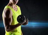 sport, bodybuilding, training and people concept - close up of young man with dumbbell flexing biceps over dark background