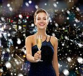 drinks, holidays, christmas, people and celebration concept - smiling woman in evening dress with glass of sparkling wine over snowy city background