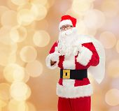 christmas, holidays, gesture and people concept - man in costume of santa claus with bag showing thumbs up over beige lights background