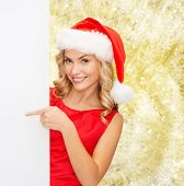 winter holidays, christmas, advertising and people concept - smiling young woman in santa helper hat with white blank billboard over yellow lights background