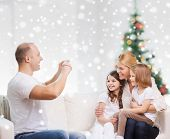 family, holidays, technology and people - smiling mother, father and little girls with camera photographing at home