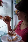 pic of greedy  - Young greedy woman and delicous dessert at night  - JPG
