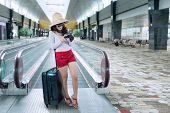 Female Tourist On Escalator At Airport
