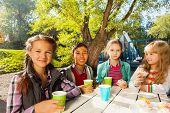 International children drink tea from cups outside