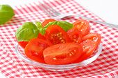 detail of tomato salad with basil on checkered dishtowel