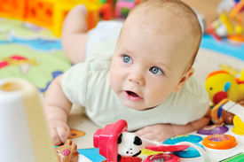 image of playmate  - a baby on the carpet with toys - JPG