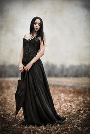 stock photo of gothic girl  - A beautiful sad goth girl holds black umbrella - JPG