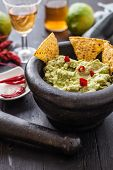 pic of nachos  - black stone bowl with fresh guacamole and nachos for dip - JPG