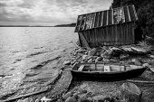 foto of old boat  - Old wooden fishing boat and barn on lake coast in Karelia - JPG