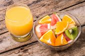 stock photo of orange-juice  - Fresh fruit salad with glass of orange juice on old wooden table - JPG